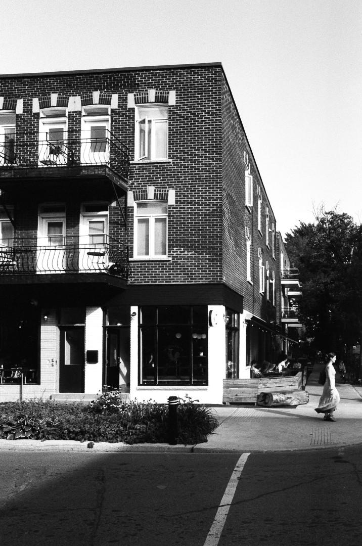 Bel éclairage et contraste entre le batiment, la rue et la jeune fille marchant sur le trotoir.  Photographie: film noir et blanc numérisé sur papier.