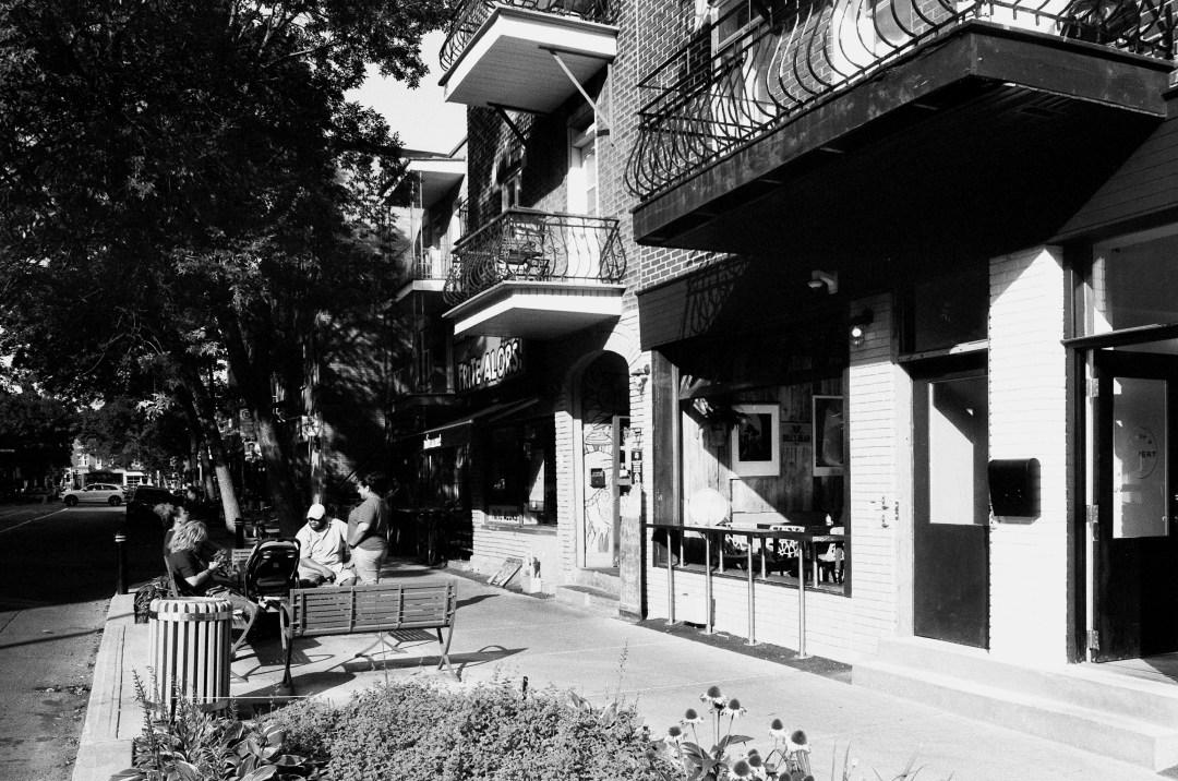 Belle oposition de contraste entre la facade du café et le feuillage des arbres.  Photographie: film noir et blanc numérisé sur papier.